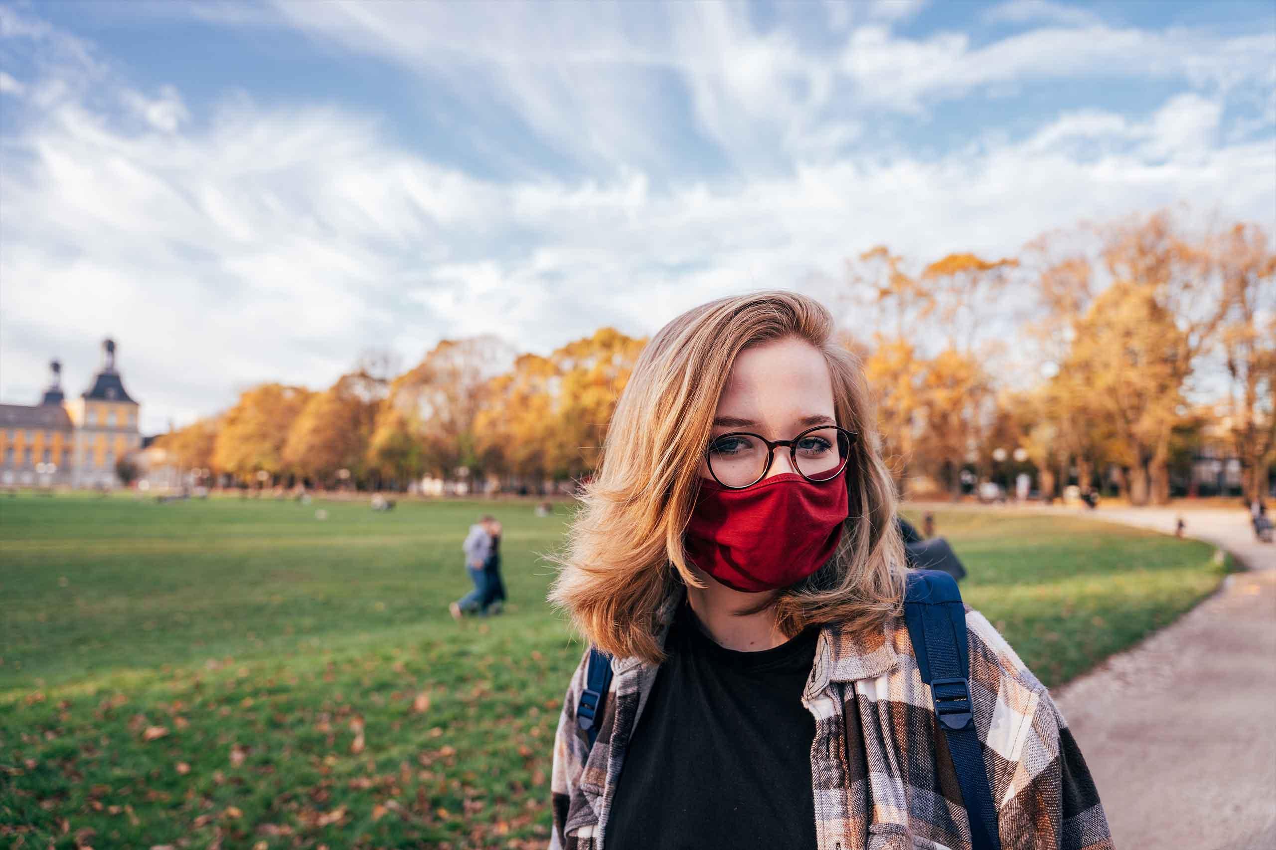 Frau mit Corona Maske in Park, England