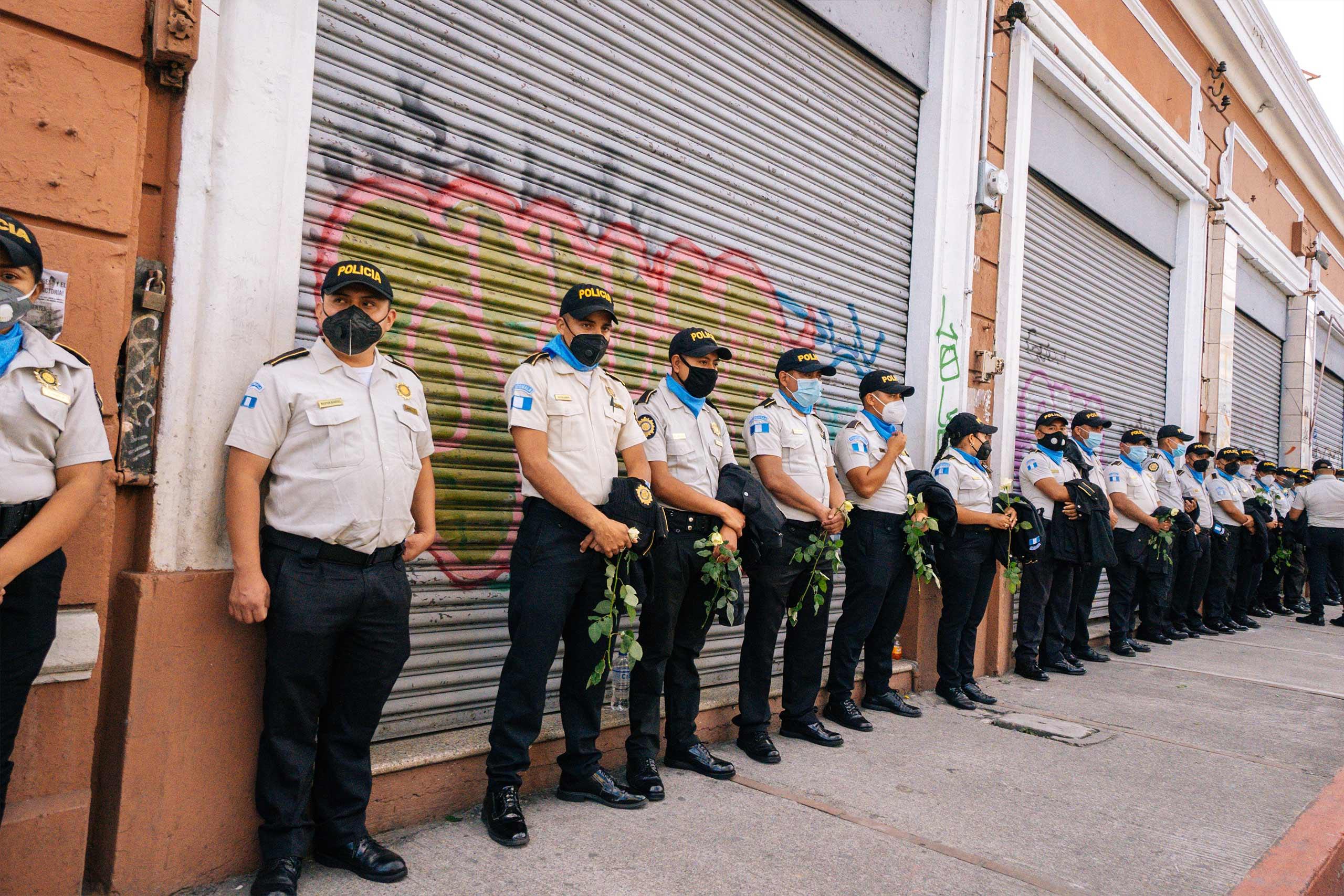 Polizsten mit Corona Masken, in Reihe vor Gebäude